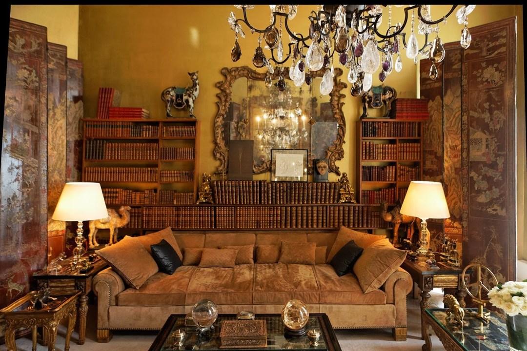 Sala da casa-atelier da estilista Coco Chanel - tudo em pares - almofadas , cor preta - lustres , bolas de cristal, animais em artesanato- e ao fundo uma enorme biblioteca de livros