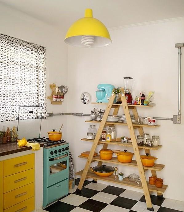cozinha com piso preto e branco apresenta fogão azul claro e geleiro amarelo. Ao fundo a prateleira é uma escada de prateleiras onde os potes e objetos coloridos enfeitam o ambiente...