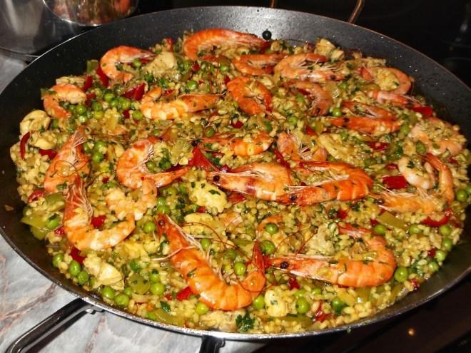 gamela grande, contendo paella que é um prato típico espanhol, que contem arroz e varios frutos do mar, camarões, mariscos e ervilhas, temperos e tomates.