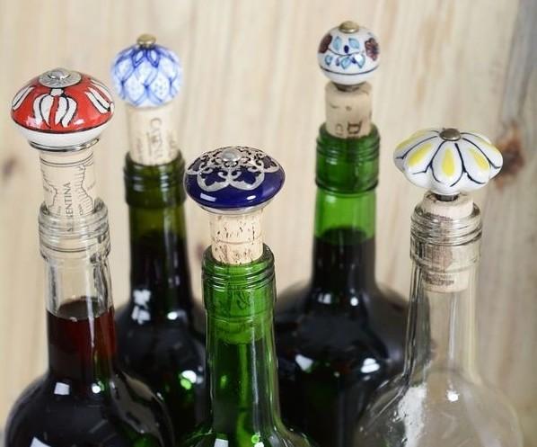 várias garrafas coloridas e transparentes com tampas de rolhas em acabamento de vidro trabalhado - esmaltado ou pintado a mão.