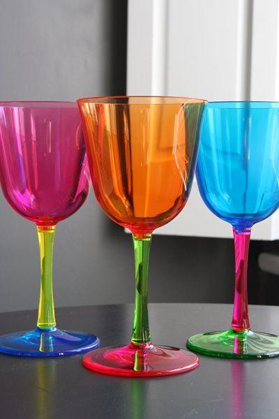 tres taças coloridas sobre uma mesa. Uma na cor pink, outra na cor laranja e a outra na cor azul, as hastes são de diversas cores e a base de outras cores.