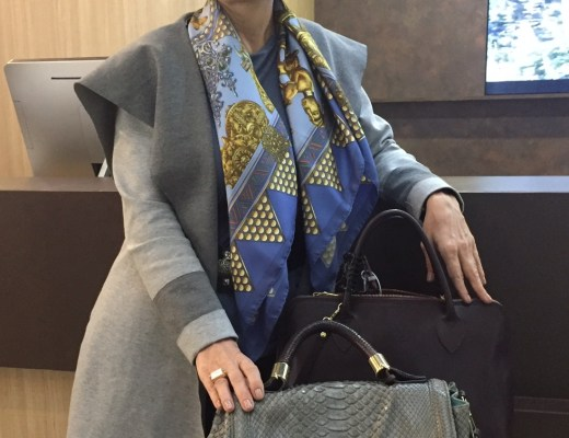 Claudia Matarazzo vestida de sobretudo cinza e lenço azul está em pé em frente a um balcão de hotel . A sua frente duas bolsas estão apoiadas em uma mesinha na frente do balcão.