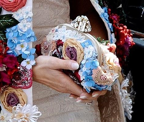 Melania Trump , esposa de Donald Trump, a porta do carro oficial. Ela usa um vestido , cor clara, e um casado com detalhes de flores 3D, de todas as cores. Ela usa óculos escuros. Em suas mãos uma bolsa pequena com os mesmo detalhes do casaco.