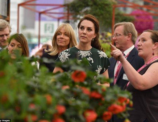 Kate Middleton, em visita a Chelsea Flowers Show, sorri para todos, usando um vestido verde escuro e com detalhes de flores na cor branca, tem seus cabelos presos, Ela está olhando a exposição junto a um grupo de pessoas.