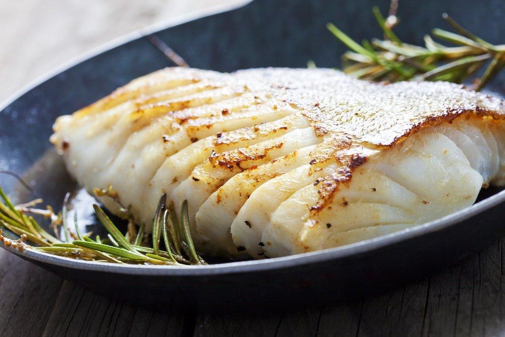 Prato redondo , de cor azul acinzentado, com um pedaço de peixe , cor branca em postas grandes, ao lado ramos de alecrim.