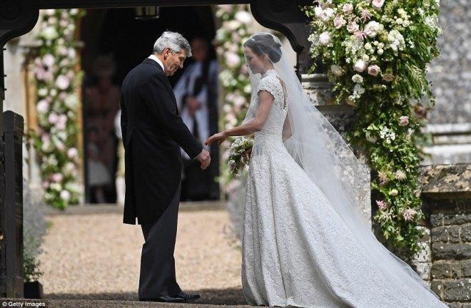 Pippa Middleton vestida de noiva em vestido tradicional branco com véu leve longo e cobrindo também o rosto está a frente de uma igreja e segura as mãos de um senhor d cabelos brancos, provavelmente seu pai.