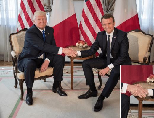 Presidente Donald Trump e o Presidente Emmanuel Macron da França, participam do Encontro Protocolar, eles estão sentados um de cada lado, com bandeiras dos dois países ao fundo, e Macron aperta a mão de Trump, fortemente, ambos vestem ternos escuros , camisas branca e gravatas em cores escuras