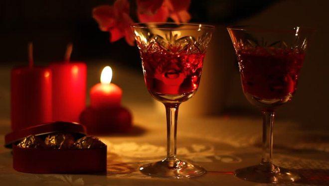 mesa decorada , num ambiente escuro, onde temos em primeiro plano duas taças decoradas, contendo vinho tinto e ao fundo velas decoram a mesa, a menor está acesa.