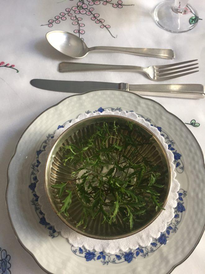 pequena cumbuca de prata sobre uma toalhinha que, por sua vez está sobre o prato de sobremesa. Na água são colocados raminhos verdes em profusão