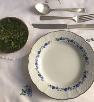 pequena cumbuca de prata com raminhos verdes e água colocada a esquerda do prato de sobremesa e ligeiramente acima