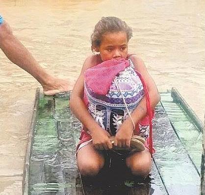 Na enchente em Pernambuco, menina de 8 anos, sobre uma tabua de madeira, que serve como barco, está ajoelhada com uma mochila abraçada ao corpo e dentro dela, seus livros e cadernos.