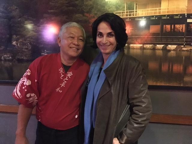 Claudia matarazzo de jaqueta de couro marrom e cabe,os castanhos curtos está abraçada ao senhor Utida um japonês de cerca de 60 anos vestido de quimono vermelho.