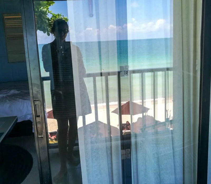 Blick durch einen Vorhang zum Strand