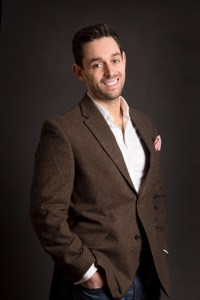 Stylish man in brown suit on black backdrop