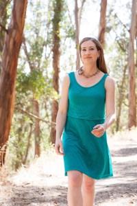 woman in green dress walking in the woods