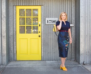 woman in a blue dress by a yellow door