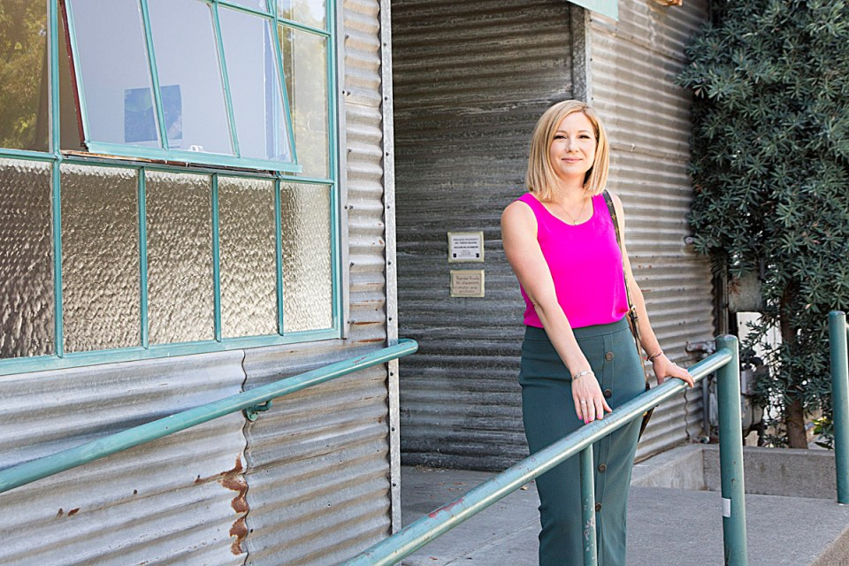 woman in pink blouse on a corrugated iron building