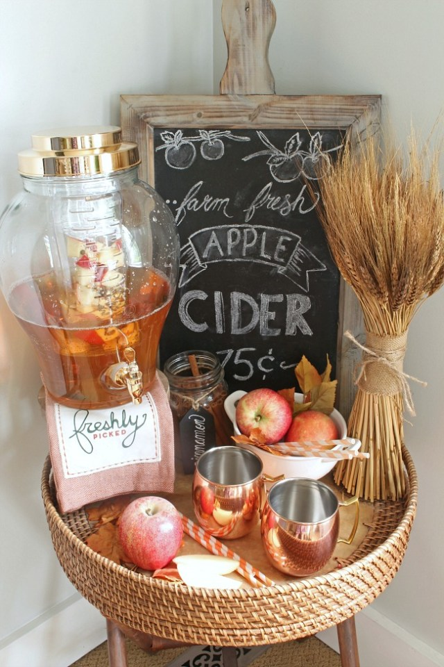 Pretty apple cider beverage bar with a chalkboard sign and decorated with coppers and neutrals.