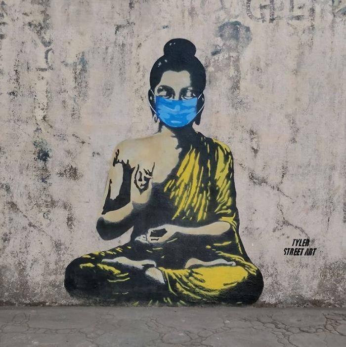 Boeddha met mondkapje op buitenmuur