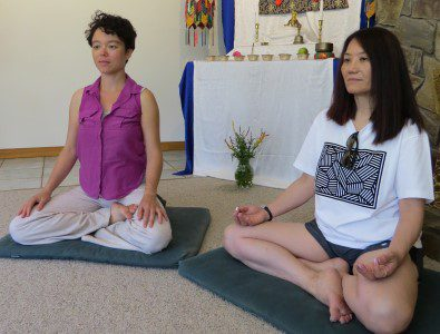 two women meditating in a shrine room