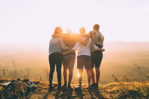 4 people hugging at sunrise