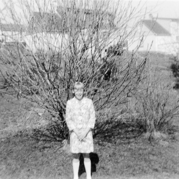 My sister Kay in front of the unbloomed forsythia, c. 1966.