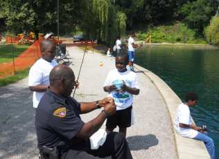 Officer Sam Anderson showing a child the proper way to put a worm on a hook.