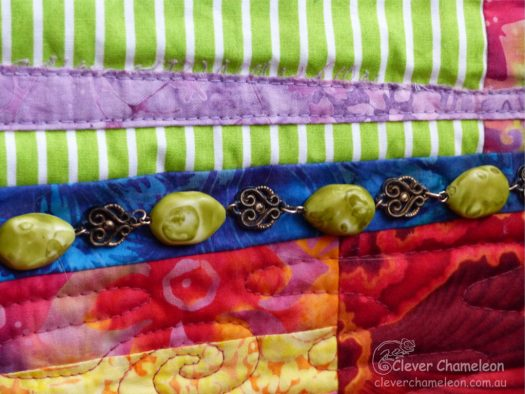Detail of Sweet Dreams wall quilt showing jewellery sewn on