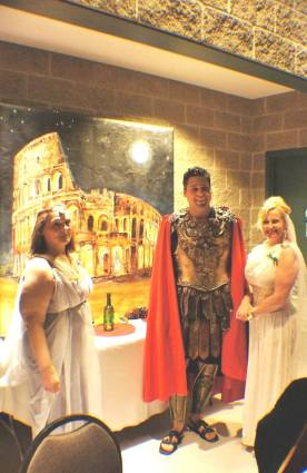 Regional Councillor Sandy Annunziata as roman soldier with Sandy Miskolzi and Dianna Hayslip in front of Melani Pyke's Roman landscape painting.