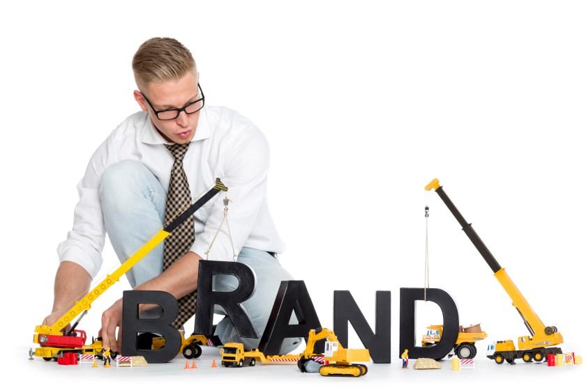 Brand start up: Businessman building brand-word.