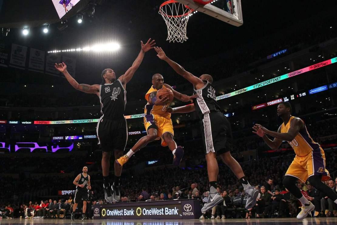 Kobe Bryant looks to make a pass between Kawhi Leonard and Boris Diaw of the San Antonio Spurs on Jan. 22, 2016.