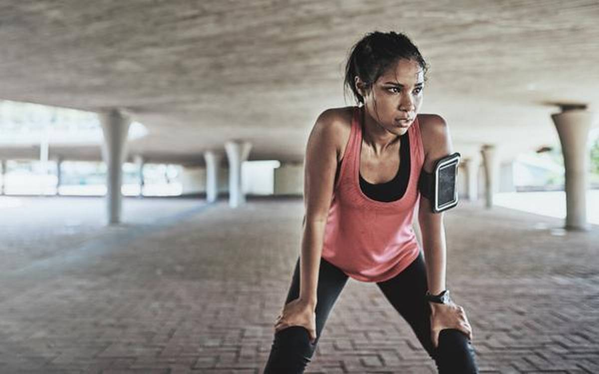 A woman working out looking tired and sweating. Is the myth the more the sweat the better the workout true?