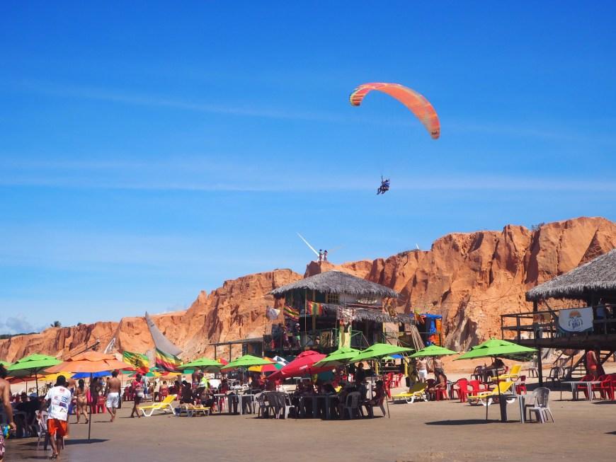 Brésil, Céara, nordeste : Plage de Canoa Quebrada, avec activités sportives comme le parapente et kitesurf.