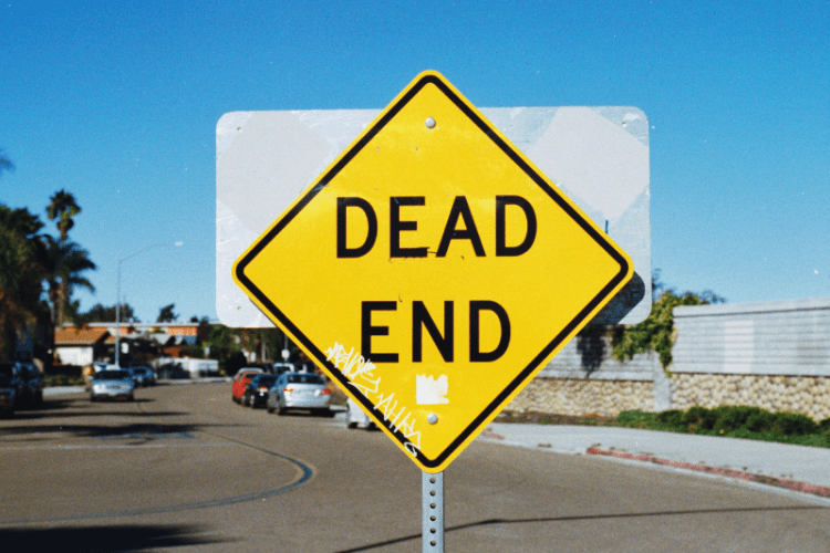 Dead end road sign with blue sky