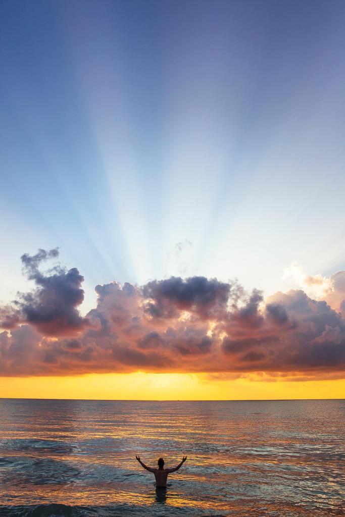 Ihminen meressä auringonlaskun aikaan