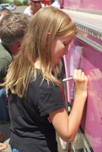 Photo by Valerie Shelton Karyn's daughter Eva signs the Pink Heals fire truck.