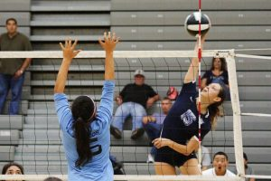 Photo by Nick Baker  Clovis East outside hitter Madison Mossette tries to pound a shot past the blocking attempt of Clovis North's Madison Graville in the championship match of the Hard Driven Volleyball Challenge won by the Timberwolves.