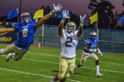 Clovis High defender Dyllon Hudec (No. 6) leaps and knocks down a pass intended for Burbank of Sacramento's DJ Johnson as Cyrus Manley (No. 23) looks on. [Photo by Nick Baker]
