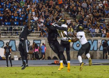 Clovis North's No. 5 David Akande goes high to intercept an Edison pass, but the play was called back due to a roughing-the-passer call. [Photo by Nick Baker]