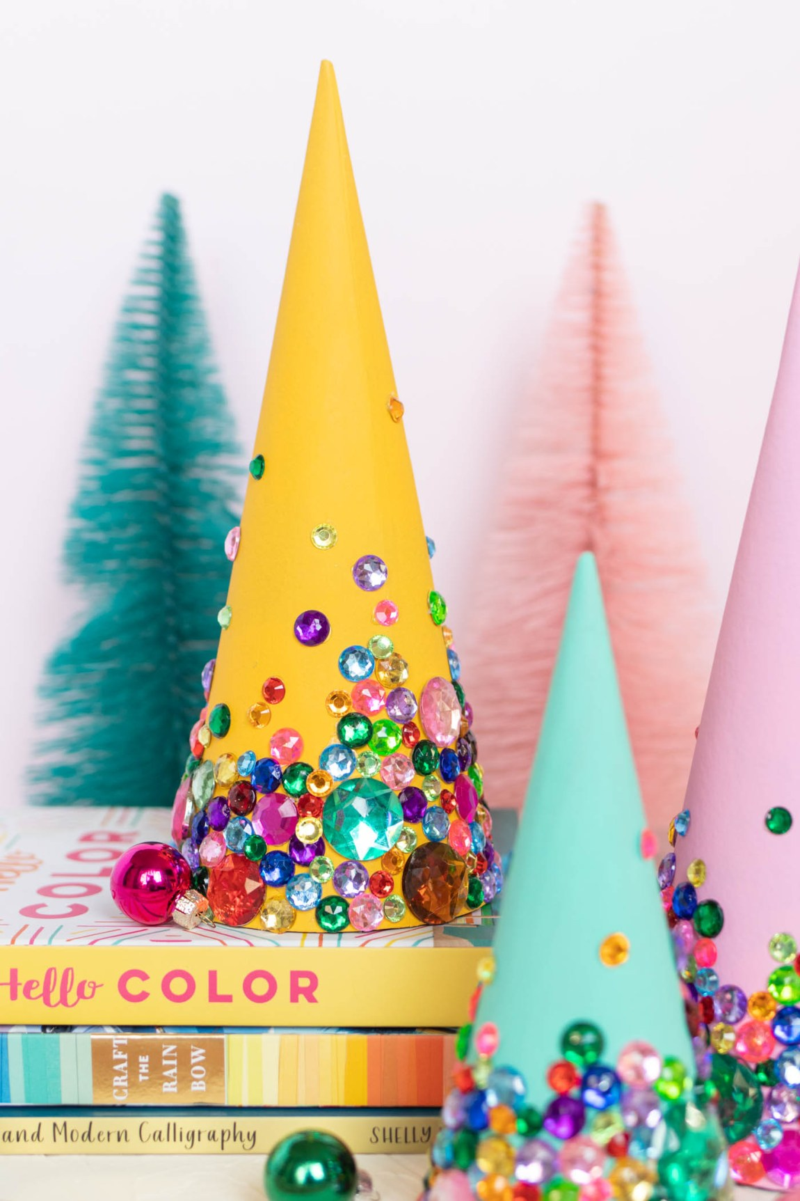 DIY Colorful Rhinestone Tree Decorations // Decorate mache cones with colorful paint and rhinestones to make sparkly tree decorations! These easy DIY Christmas trees make great mantel decor or shelf accessories for the holiday season! #christmasdiy #christmas #christmasdecor #painting #rhinestones #holidaydecor