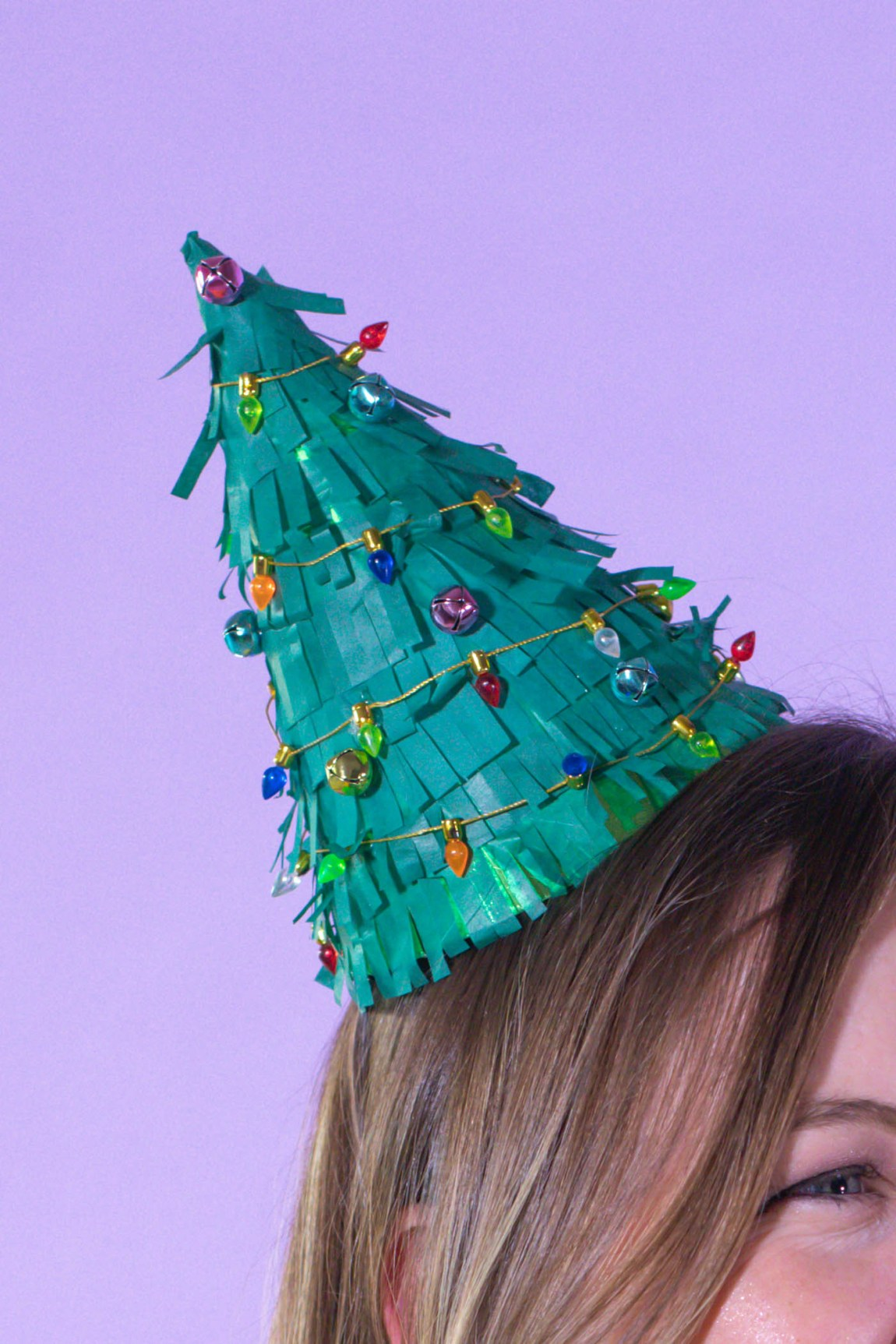 DIY Christmas Tree Party Hats // Turn a plain party hat into a fun holiday craft with tissue paper! Upcycle your hats into fringed Christmas trees decorated with lights and ornaments! #christmas #christmasdiy #christmascrafts #partydiy #partyideas #holidayparty #christmasparty #partyhats