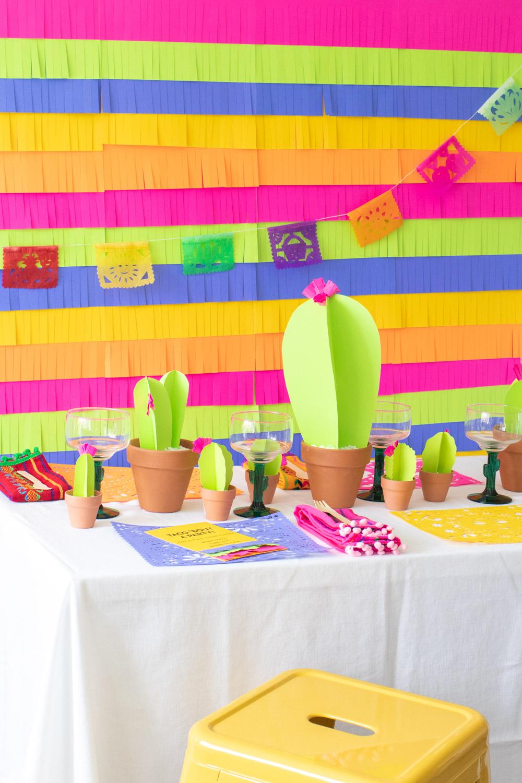 assortment of colorful paper fiesta decor, paper cacti, cacti glassware