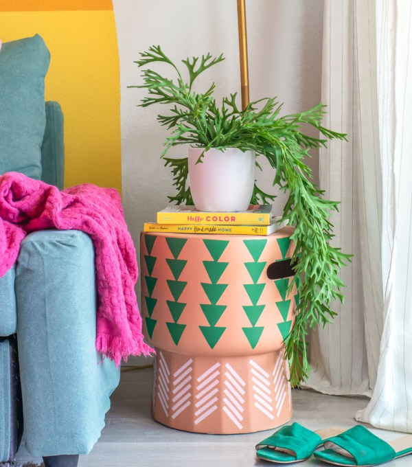 stenciled side table with books and plant in living room