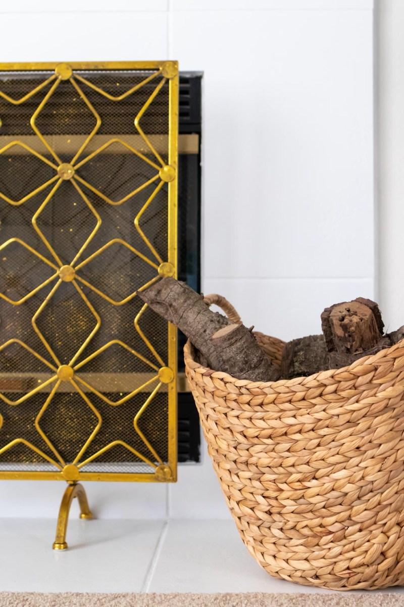 firewood in basket next to modernized fireplace