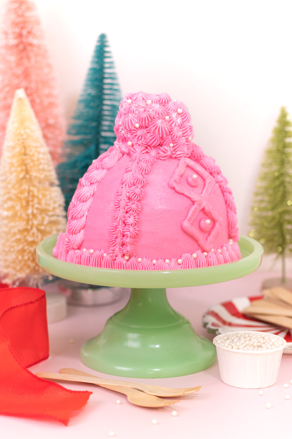knit beanie cake on cake stand in front of christmas trees