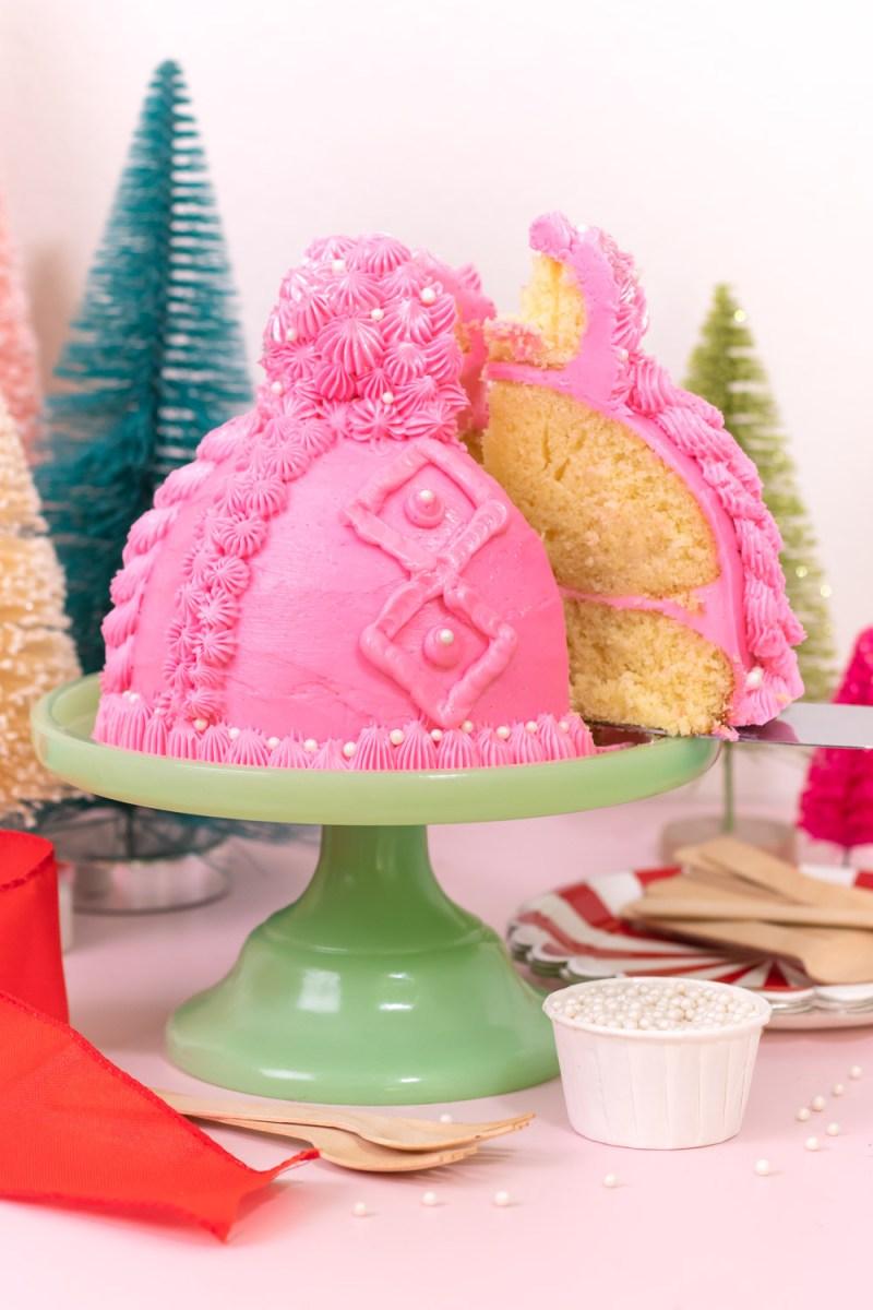 removing slice of winter hat cake with pom pom cupcake topper