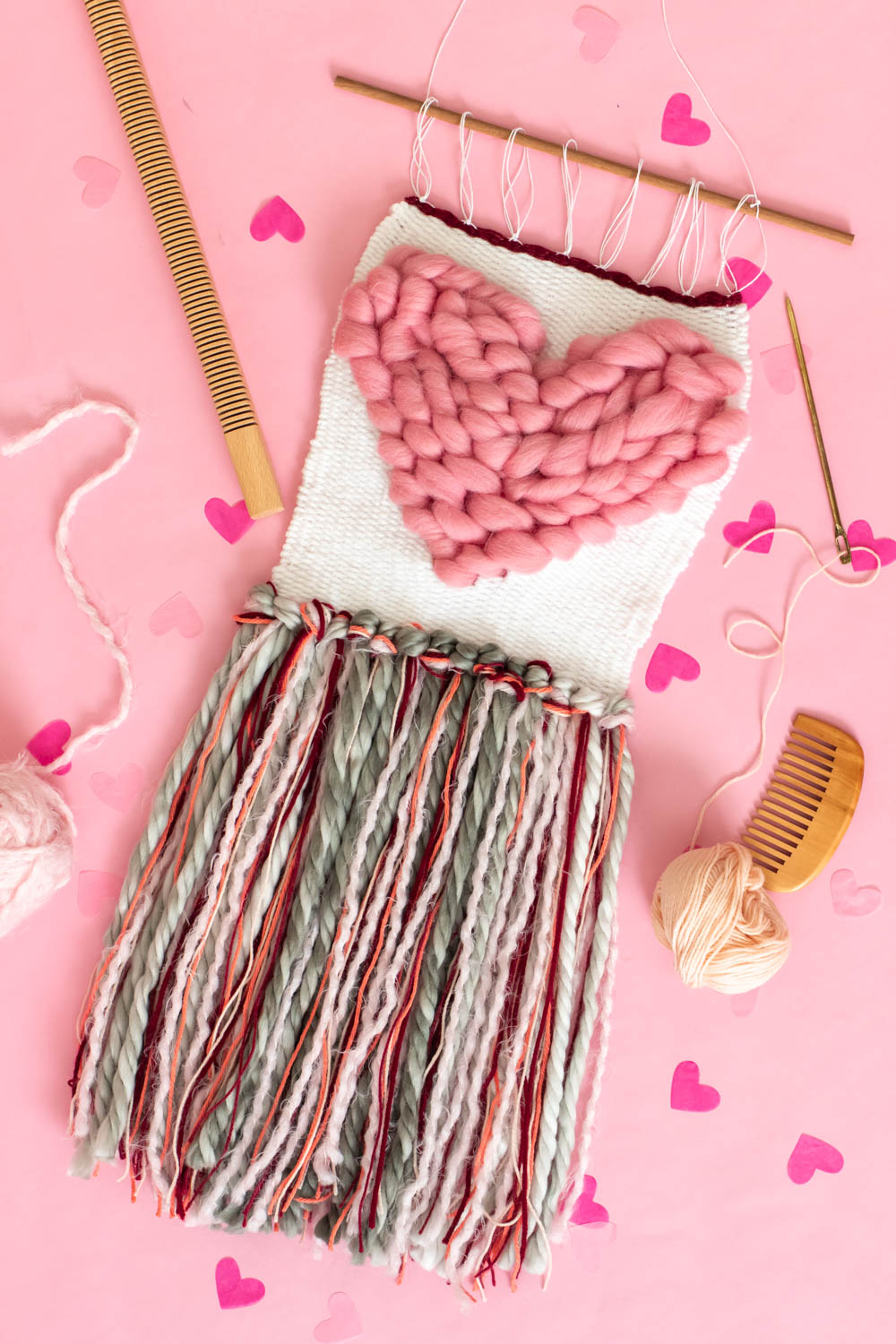 flatlay of heart weaving decor on pink background