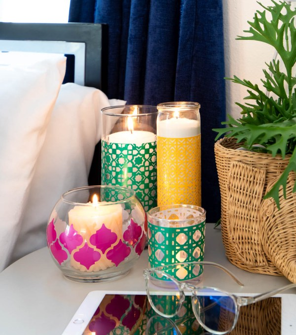 multiple boho candleholders on nightstand with tablet