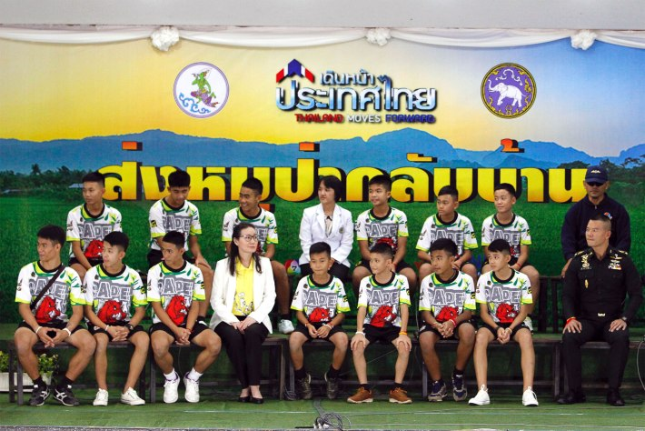 Mandatory Credit: Photo by PONGMANAT TASIRI/EPA-EFE/REX/Shutterstock (9764735a) Twelve rescued members of the Wild Boar soccer team and their assistant coach sit with Thai health officers and soldiers to make their first public appearance during a military governmental TV pool broadcasting program at Chiang Rai Provincial Administrative Organization in Chiang Rai province, Thailand, 18 July 2018. The thirteen members of Wild Boar child soccer team, including their assistant coach, who were trapped in the Tham Luang cave since 23 June 2018, made their first appearance on the day for a tightly-controlled interview with the media after they were rescued, before returning to their homes with families. Press conference of 13 members of child soccer team after rescued from Tham Luang cave, Chiang Rai, Thailand - 18 Jul 2018