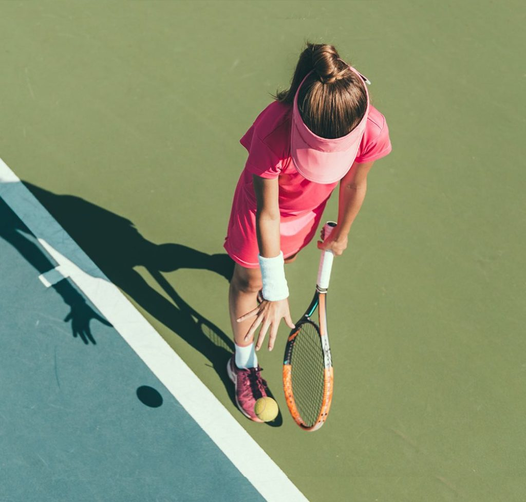 Woman playing tennis on tennis court